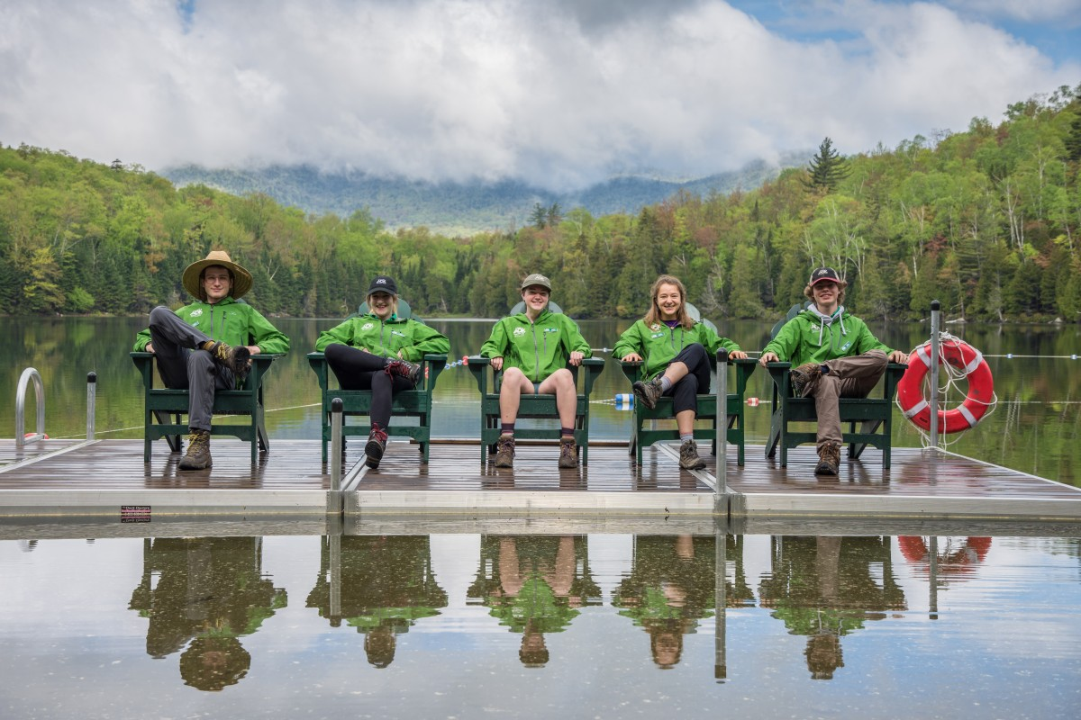 All five summer naturalists sit on the dock on Heart Lake