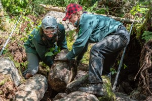 Two trail crew members manuever a boulder into position