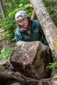A trail crew member pushes a small boulder