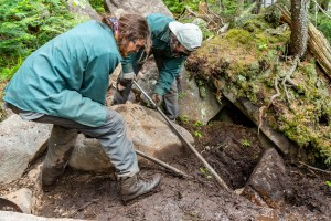 Two trail crew members use rock bars to lift a rock out of a ditch