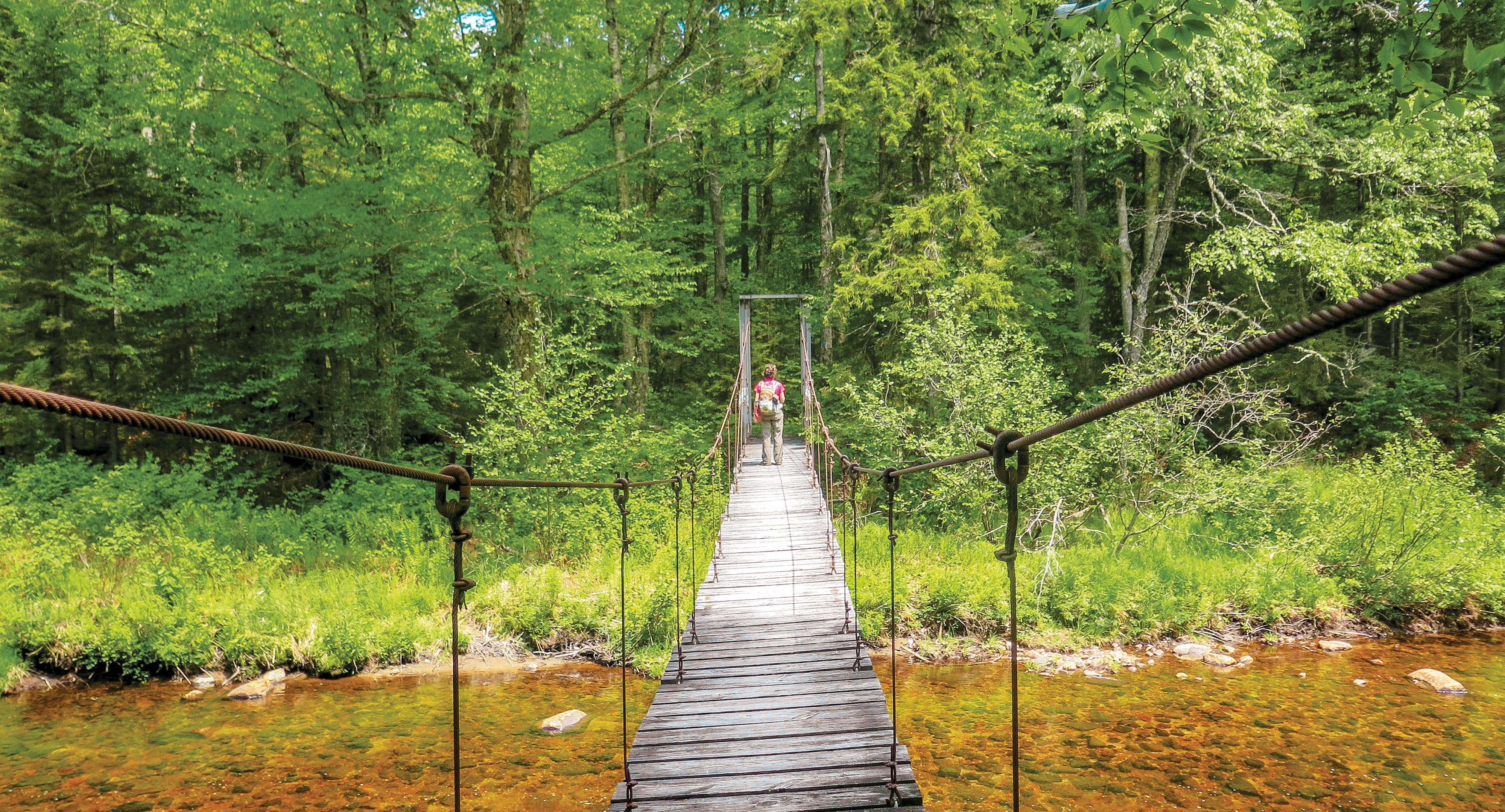 A woman has almost finished crossing a weathered wooden suspension bridge over a body of water