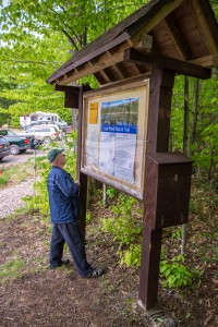 A visitor looks at the new interpretive kiosk at the trailhead