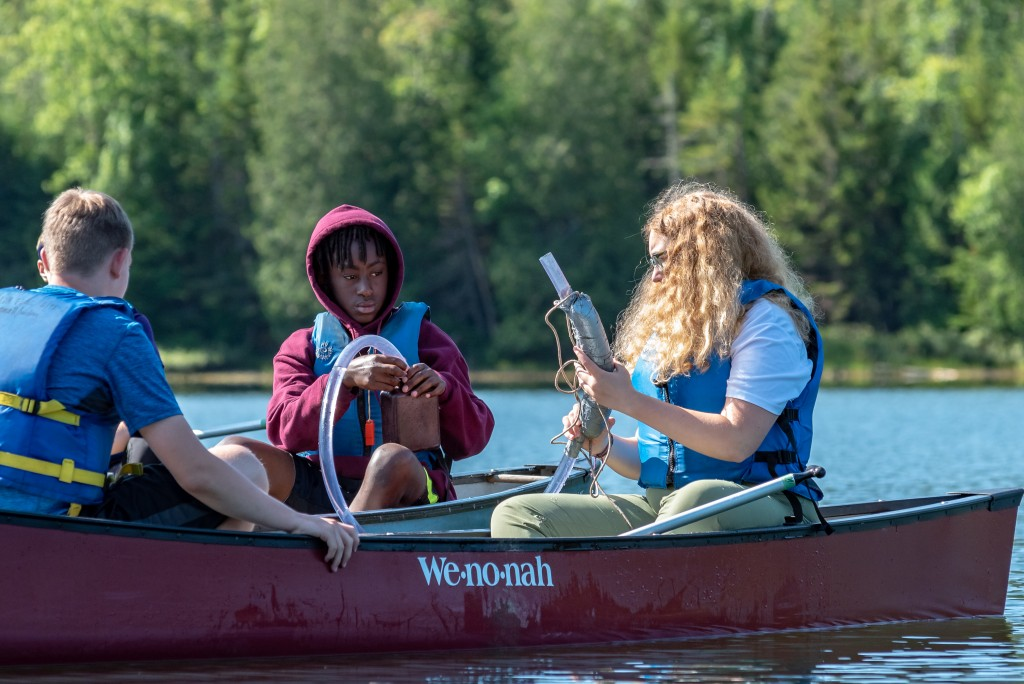 A girl and a boy perform a water quality test in Heart Lake