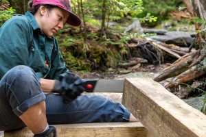 A trail crew member cuts into a piece of lumber