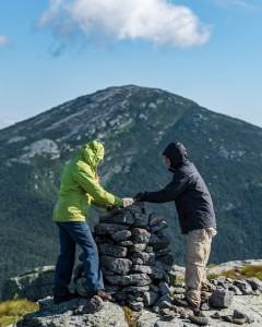 Two trail crew members building a cairn with Mt Marcy in the background