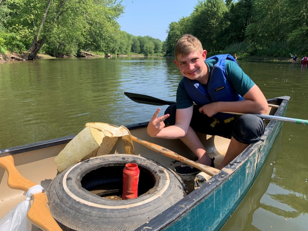 A young man collecting trash by canoe in the Ausable River