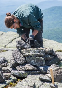 A trail crew member building a cairn