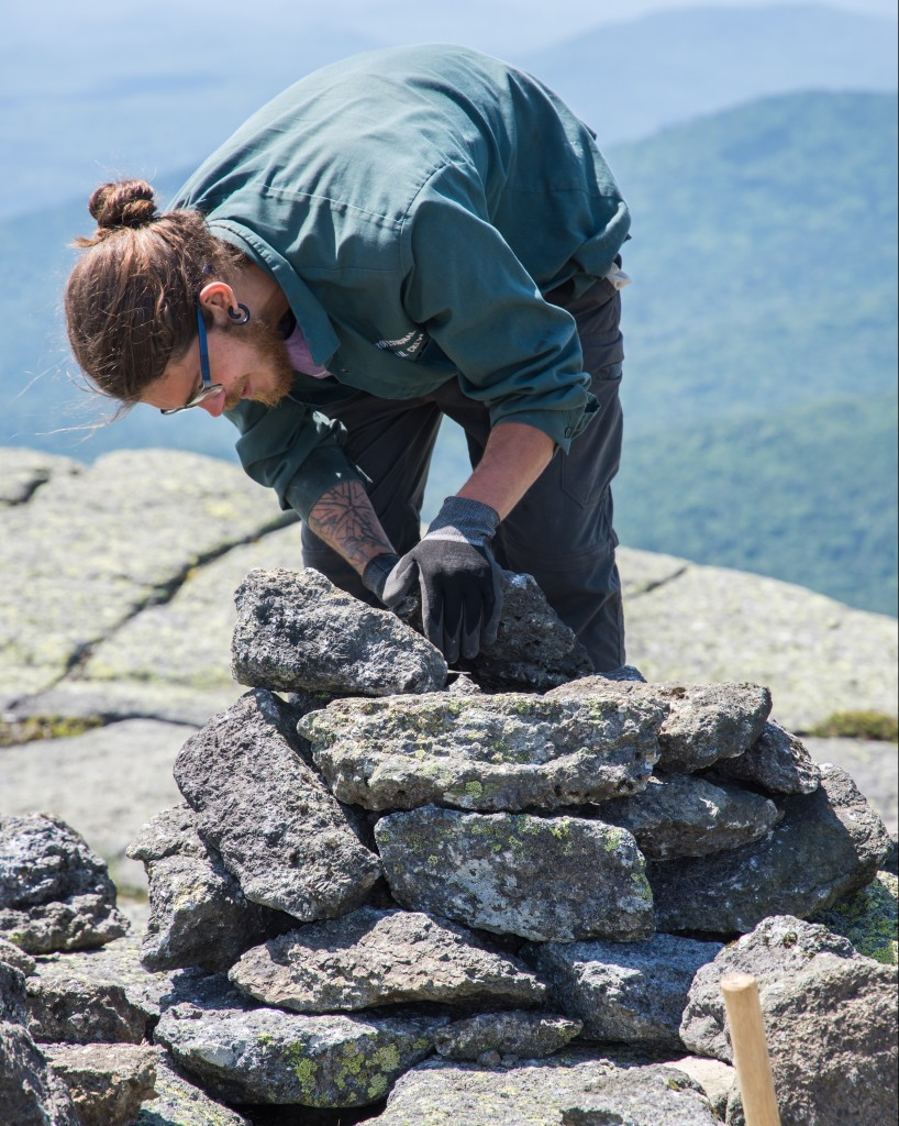 A trail crew member builds a cairn