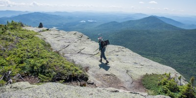 A woman walks on a summit with a load of rock