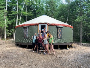 """""""The Crew"""" posing in front of a new education yurt"""