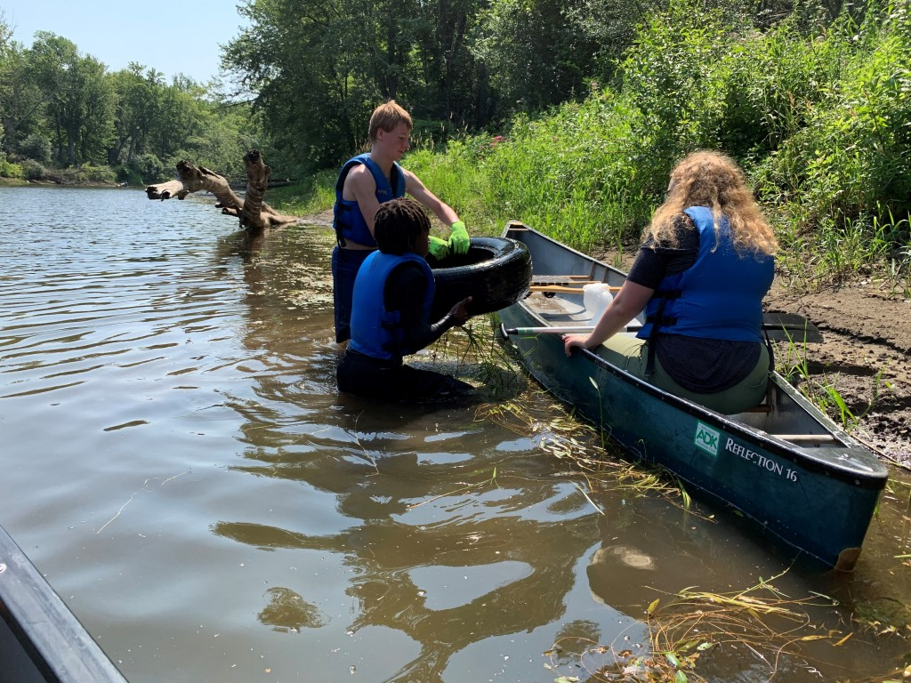 Participants pull a tire out of the river