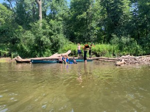 Participants haul a traffic cone out of the Ausable River