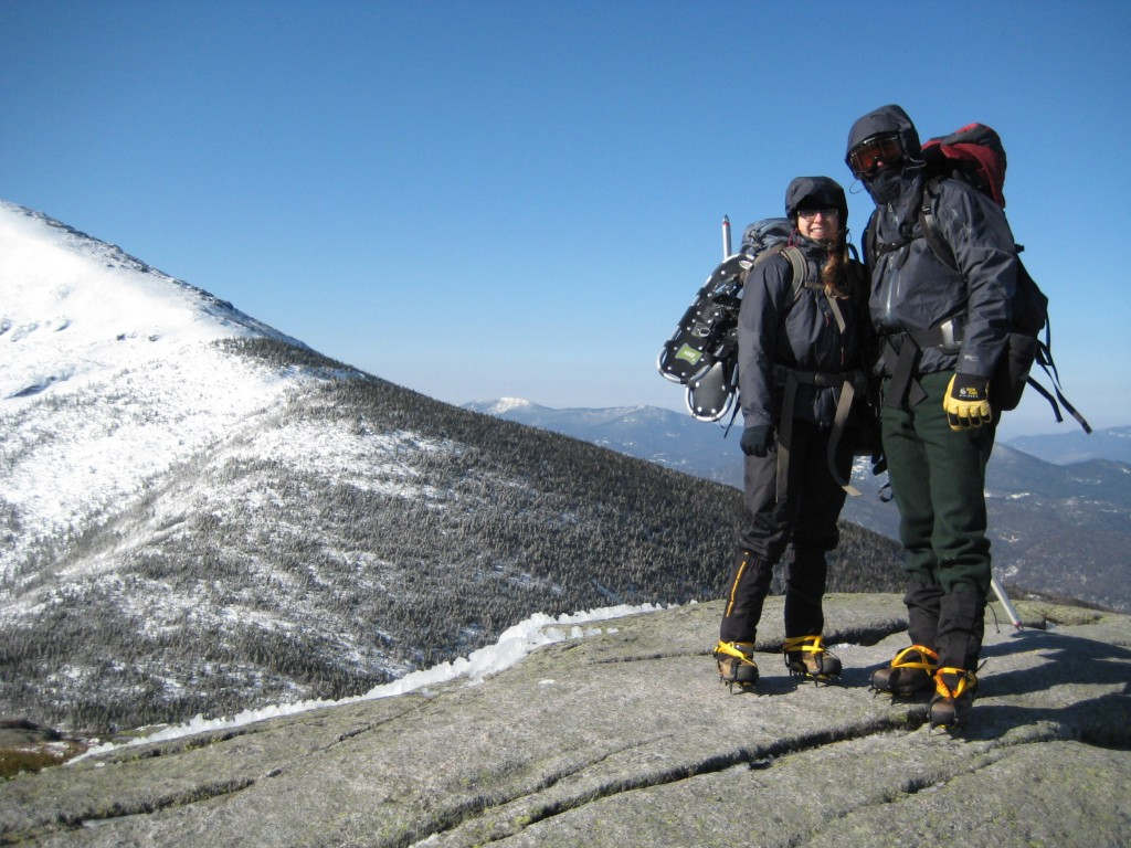 A couple stands on an icy summit with full winter gear on