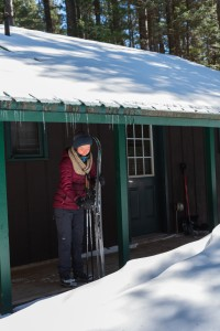 A woman prepares her skis under an awning