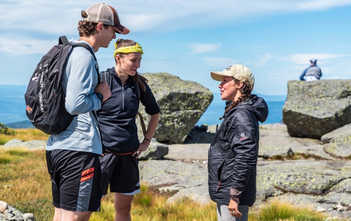 A summit steward speaks with two hikers