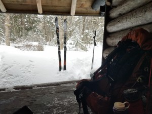 A backpack in a leanto with skis outside