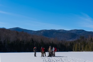 A group of people stand in a circle on a frozen lake