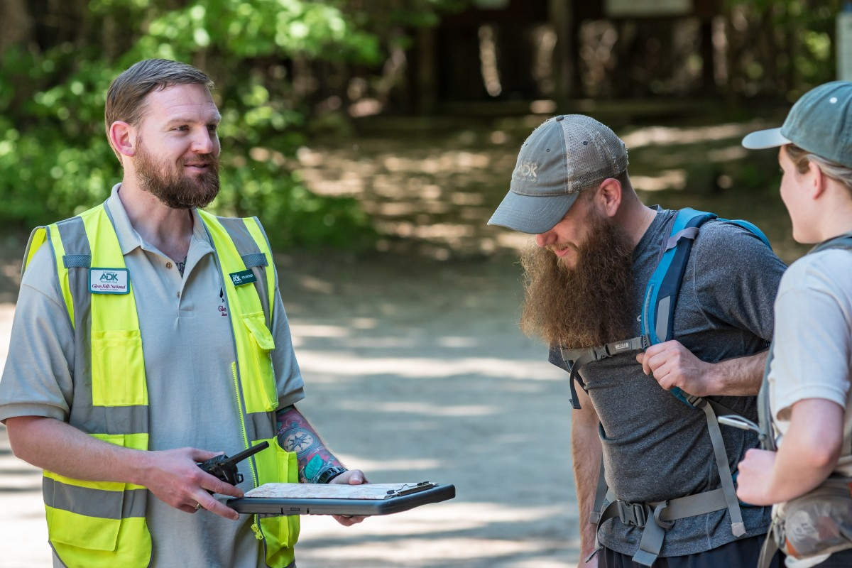 A volunteer speaks to two hikers at the trailhead