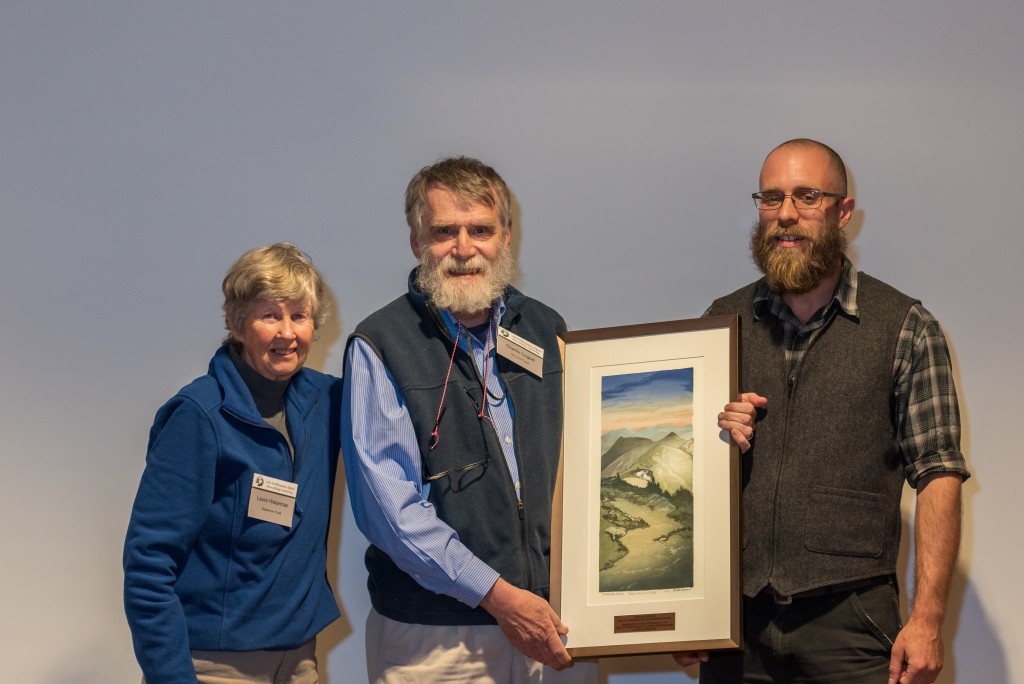 Charlie Cogbill holding a painting with two The Waterman Fund representatives