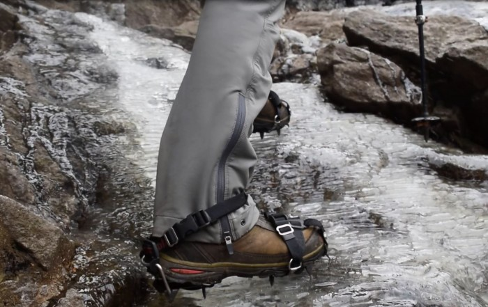 A closeup of a hikers boots showing microspikes digging into ice