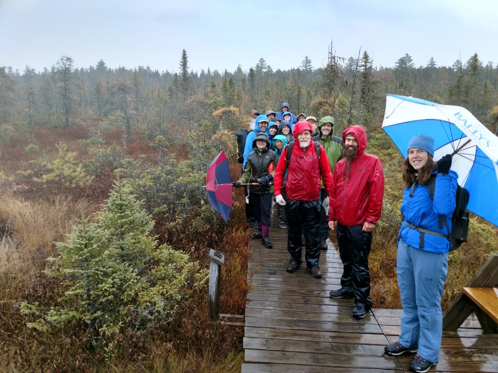 A group smiles on a board walk in the rain