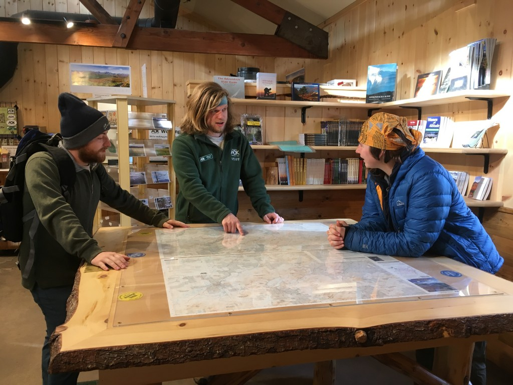 A staff member speaks to two hikers while pointing at a map table