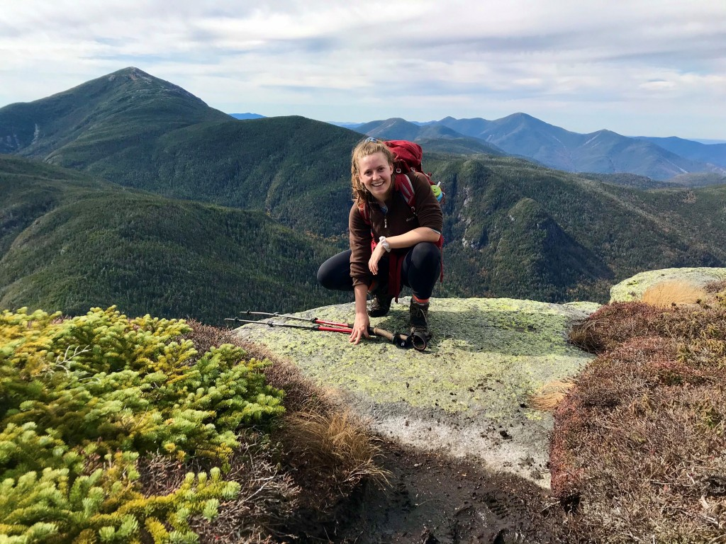 A woman crouches on a mountain summit