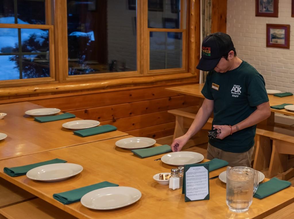 A Loj Crew member sets a table