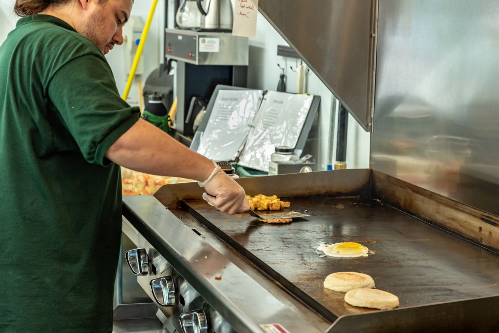 A staff member cooks eggs on a flat top