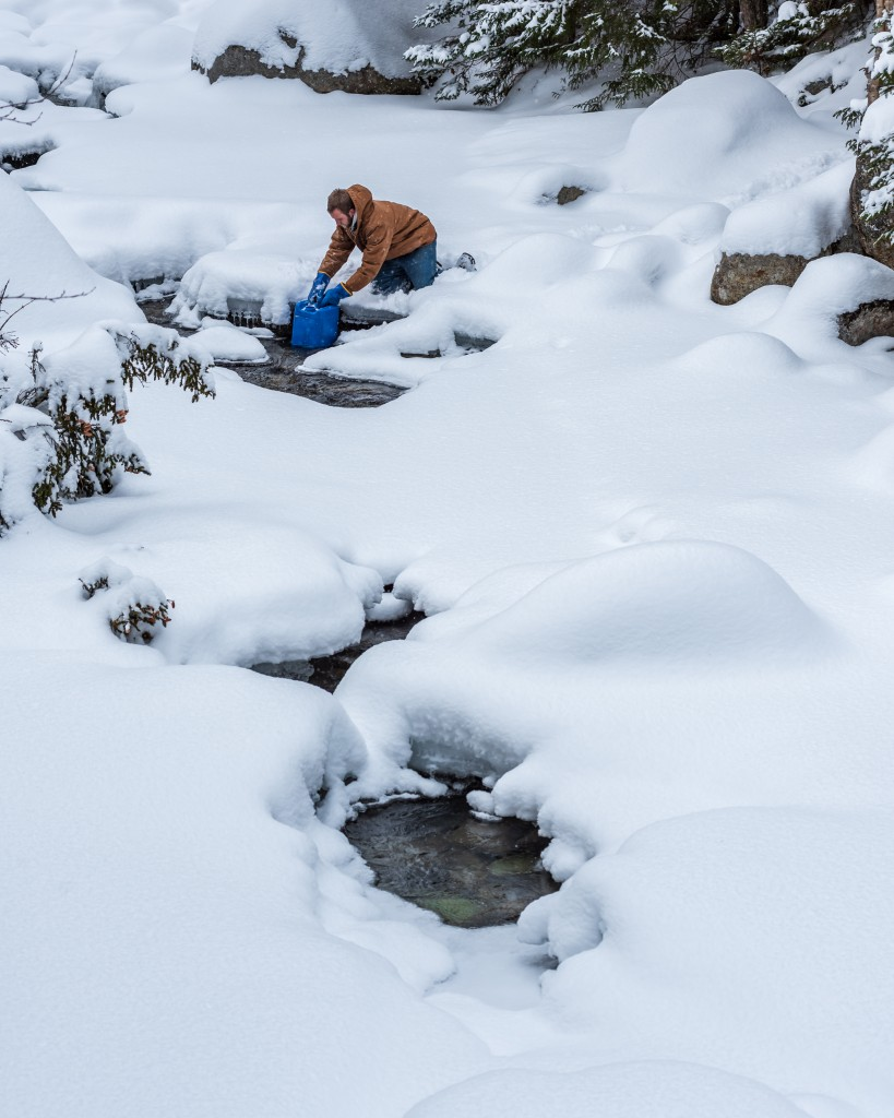 A man draws water from a frozen brook