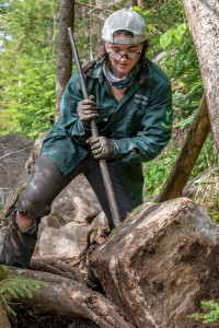 A trail crew member uses a bar to pry a rock