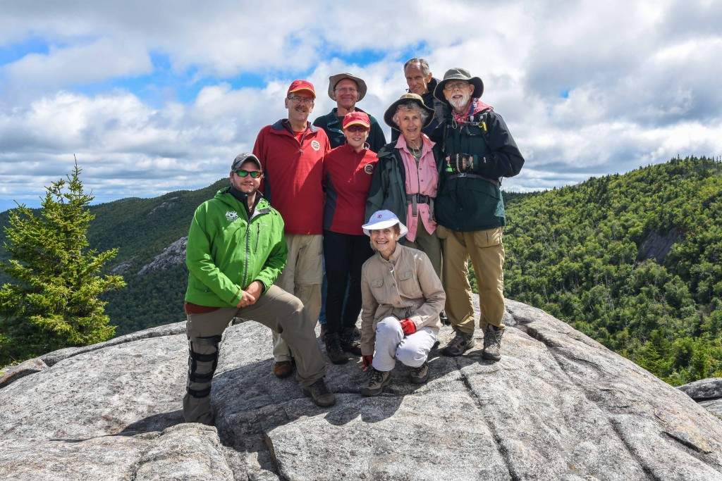 A group of road scholar hikers pose on the summit of Jay
