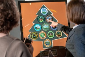 Two women look at a framed set of patches