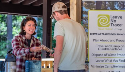 A person hands a pamphlet to a guest