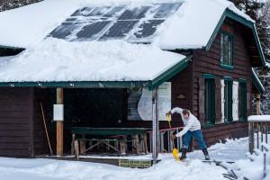 A man shovels the porch of JBL