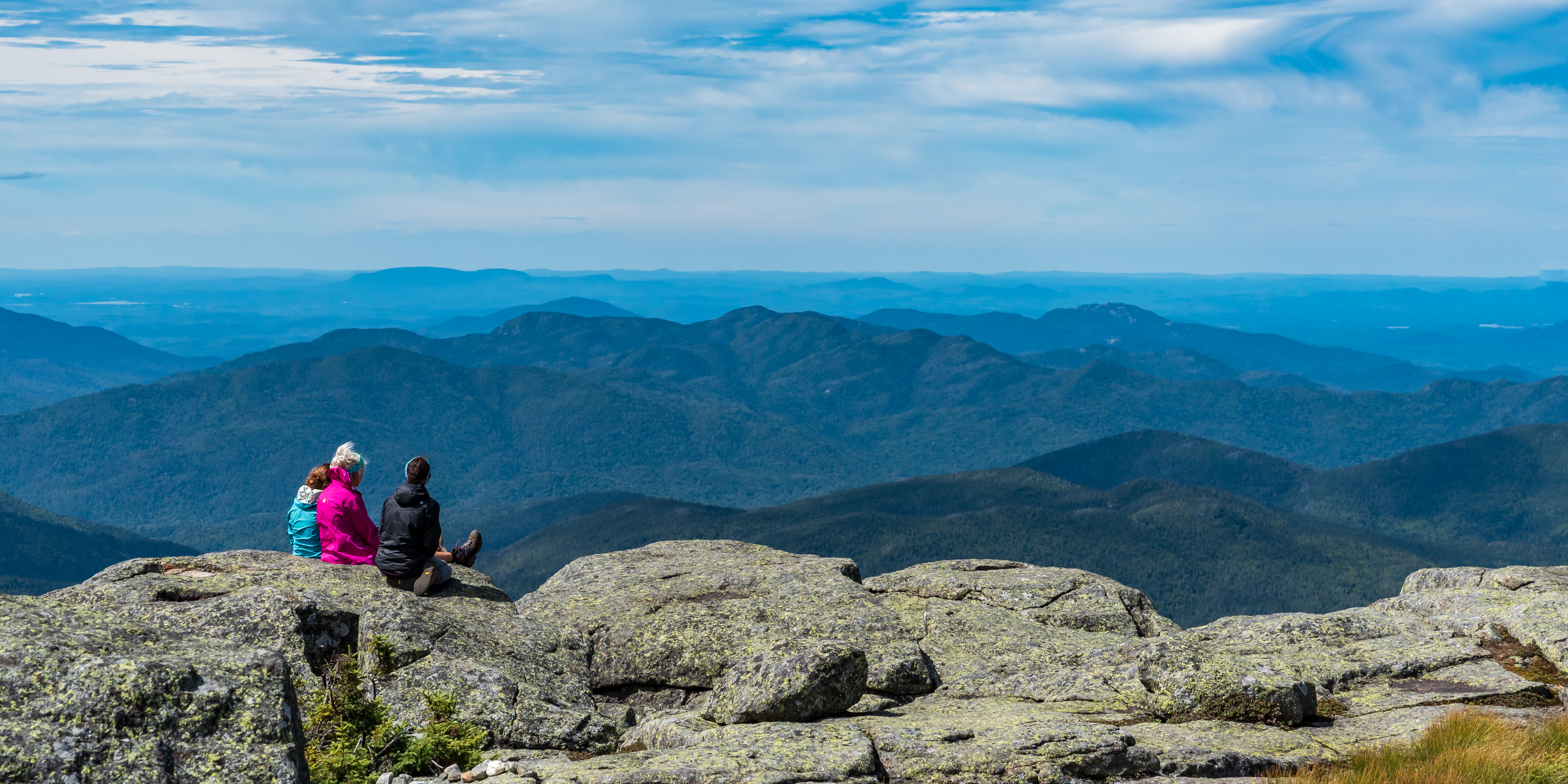A summit steward kneels next to two hikers
