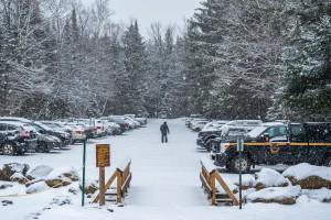 A man walks down a snowy parking lot