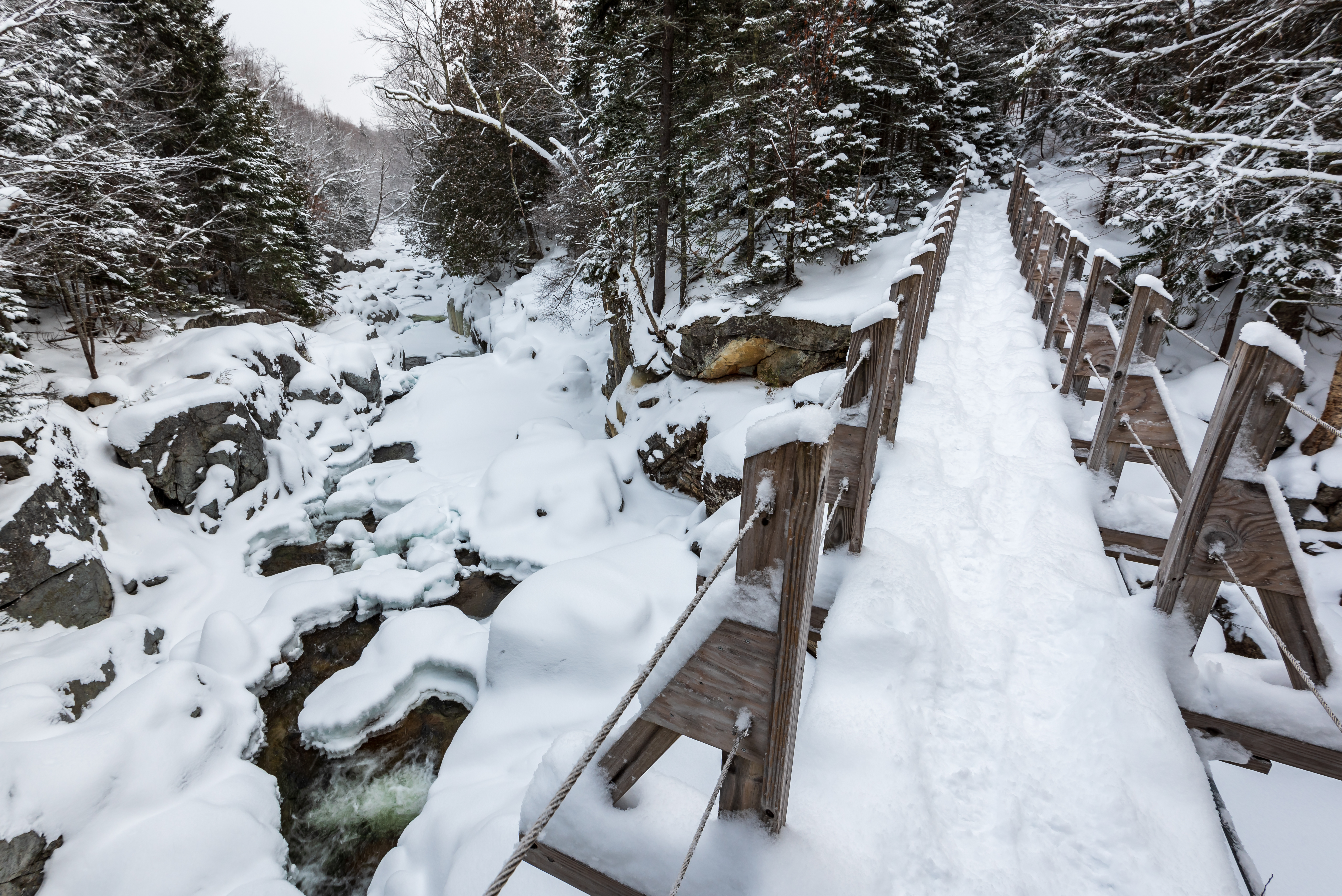 A snowy bridge over an icy river