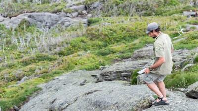 A summit steward descends a mountainside