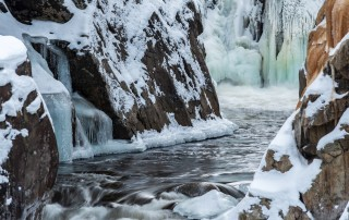 Looking down a brook towards a frozen waterfall