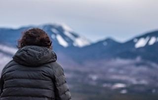 A hiker looks towards mountains
