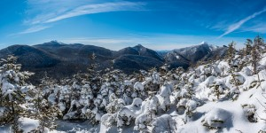 A panorama from a snow covered mountainside showing three other mountains