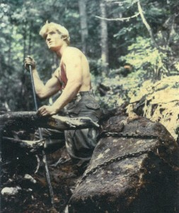 A shirtless trail worker next to a boulder