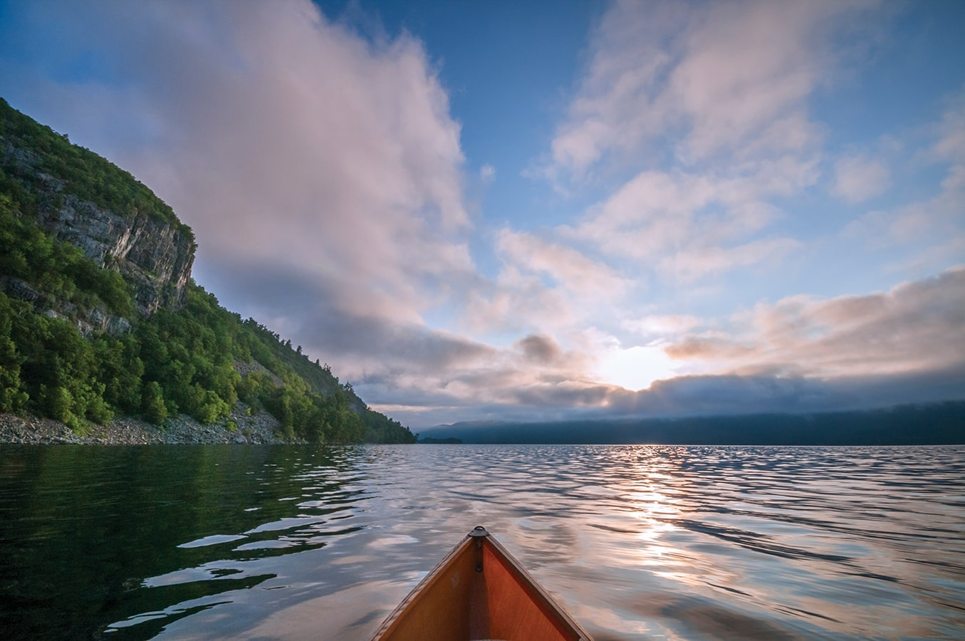 A canoe tip pointing towards a cliff and open lake