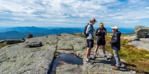 Three people stand on a summit