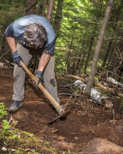 A person works on a trail with a pick