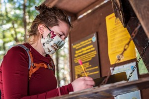 A woman signing into a trail register with a mask on