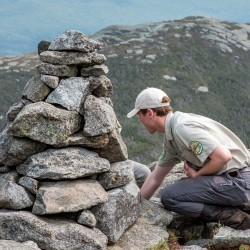 A man builds a rock cairn