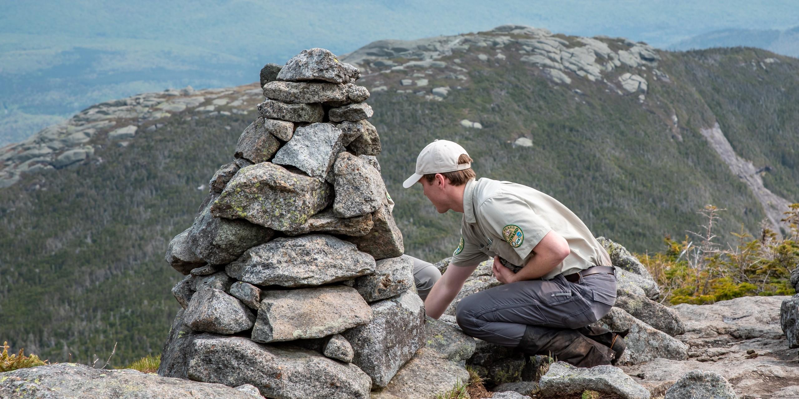 A man builds a rock cairn