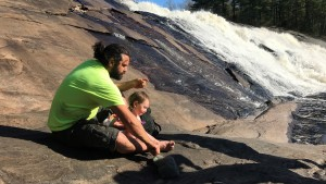 A man and a child sit by a waterfall